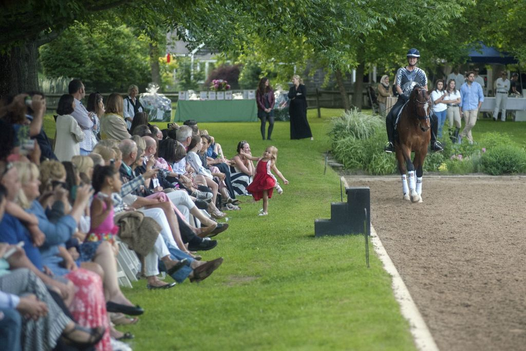 image: the crowd watches wick hotchkiss and bailey thompson  perform a dressage demo at last year's benefit