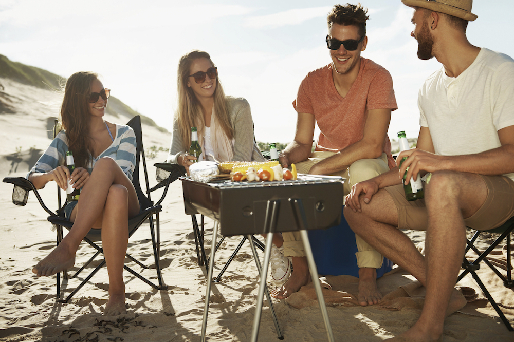 A group of young friends having a beach barbeque together on the sands. image: pixdeluxe