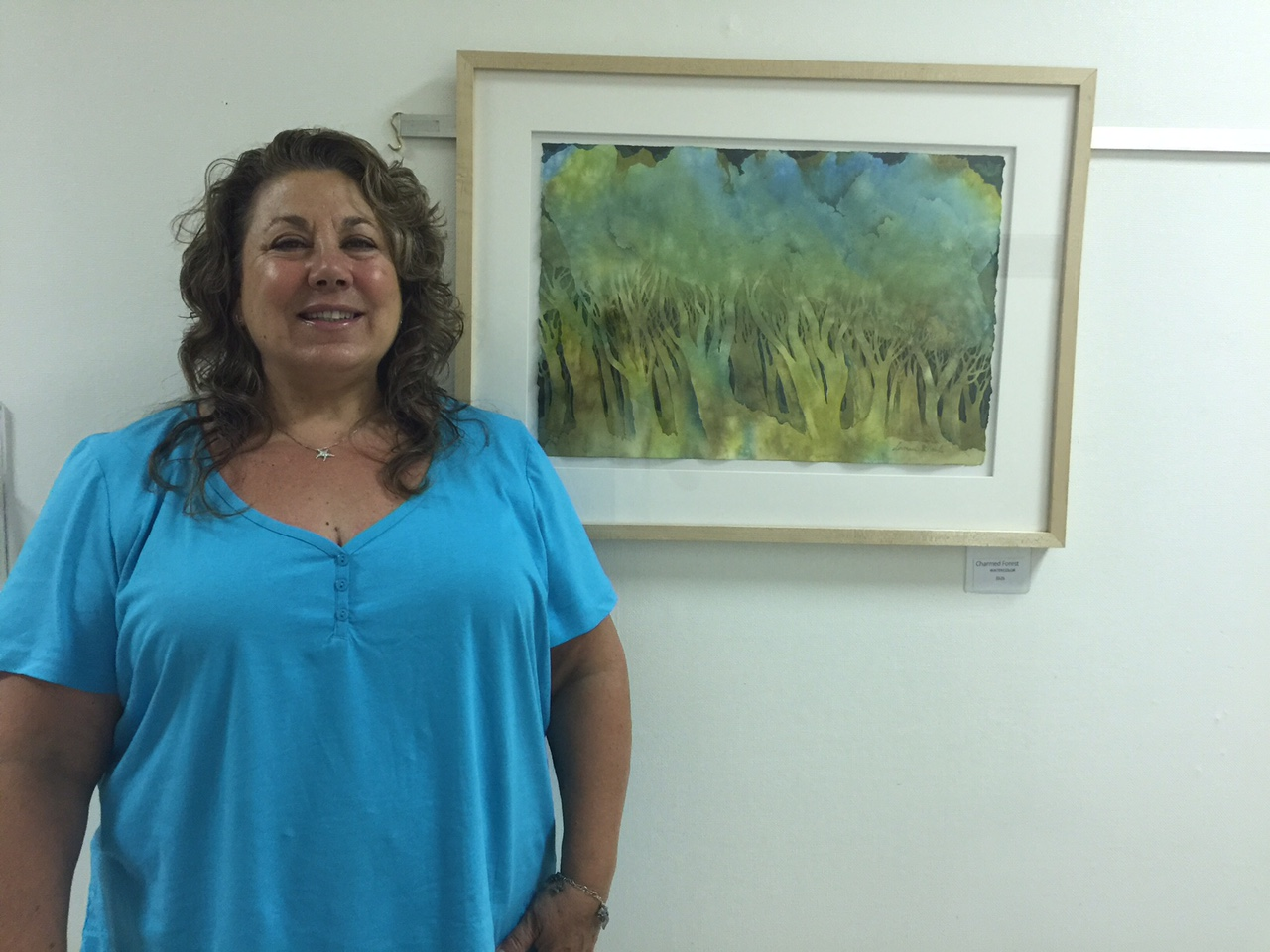"Rimmelin stands next to Charmed, a painting that ""kind of came to me as I was working on it."""