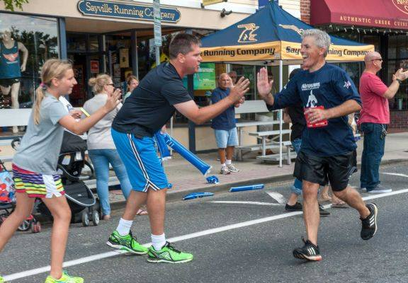 Suffolk County Executive Steve Bellone high-fives supporters in Sayville during the Suffolk County Marathon