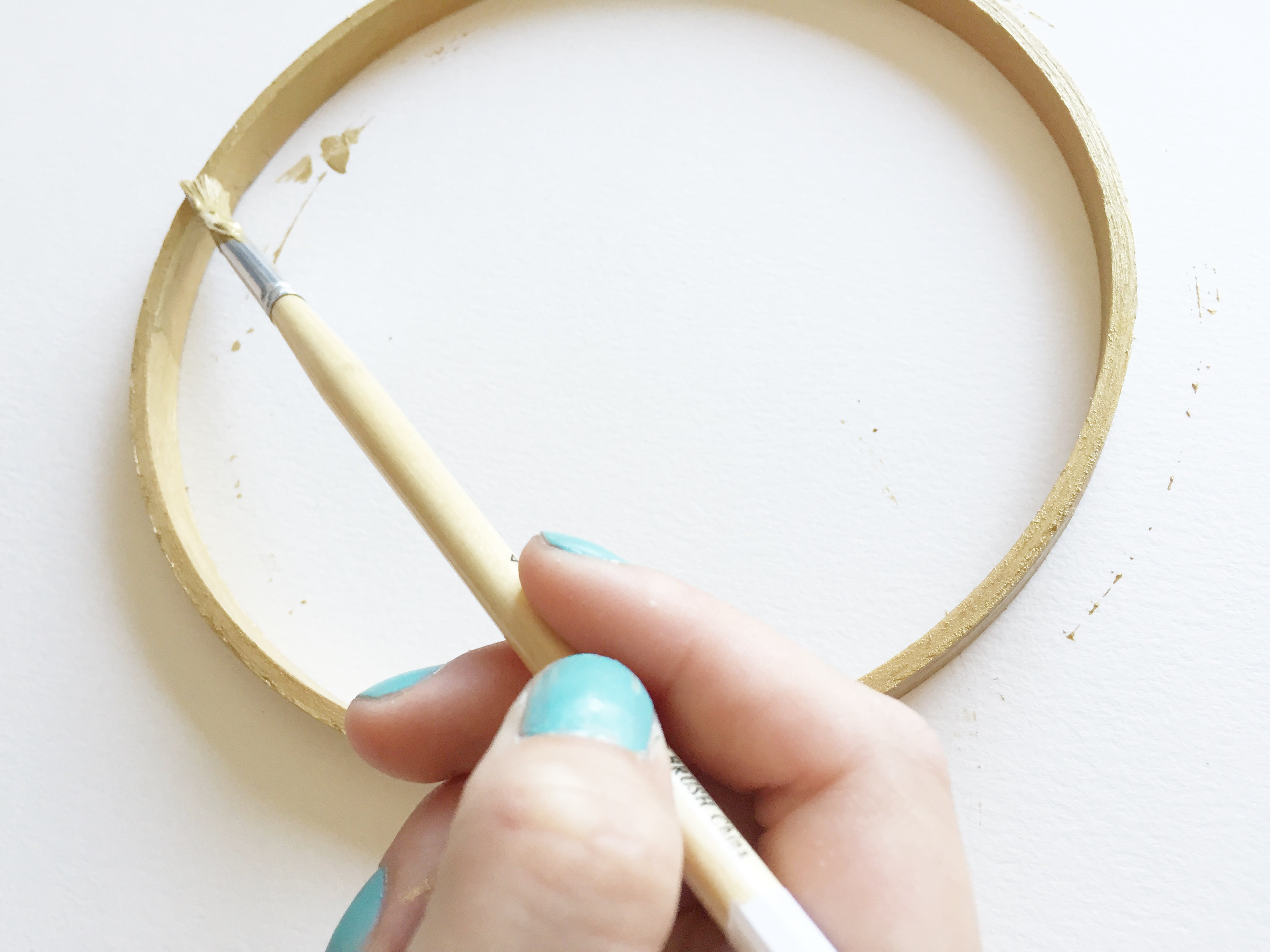 image: start by painting your wooden hoop with gold paint credit: gild collective