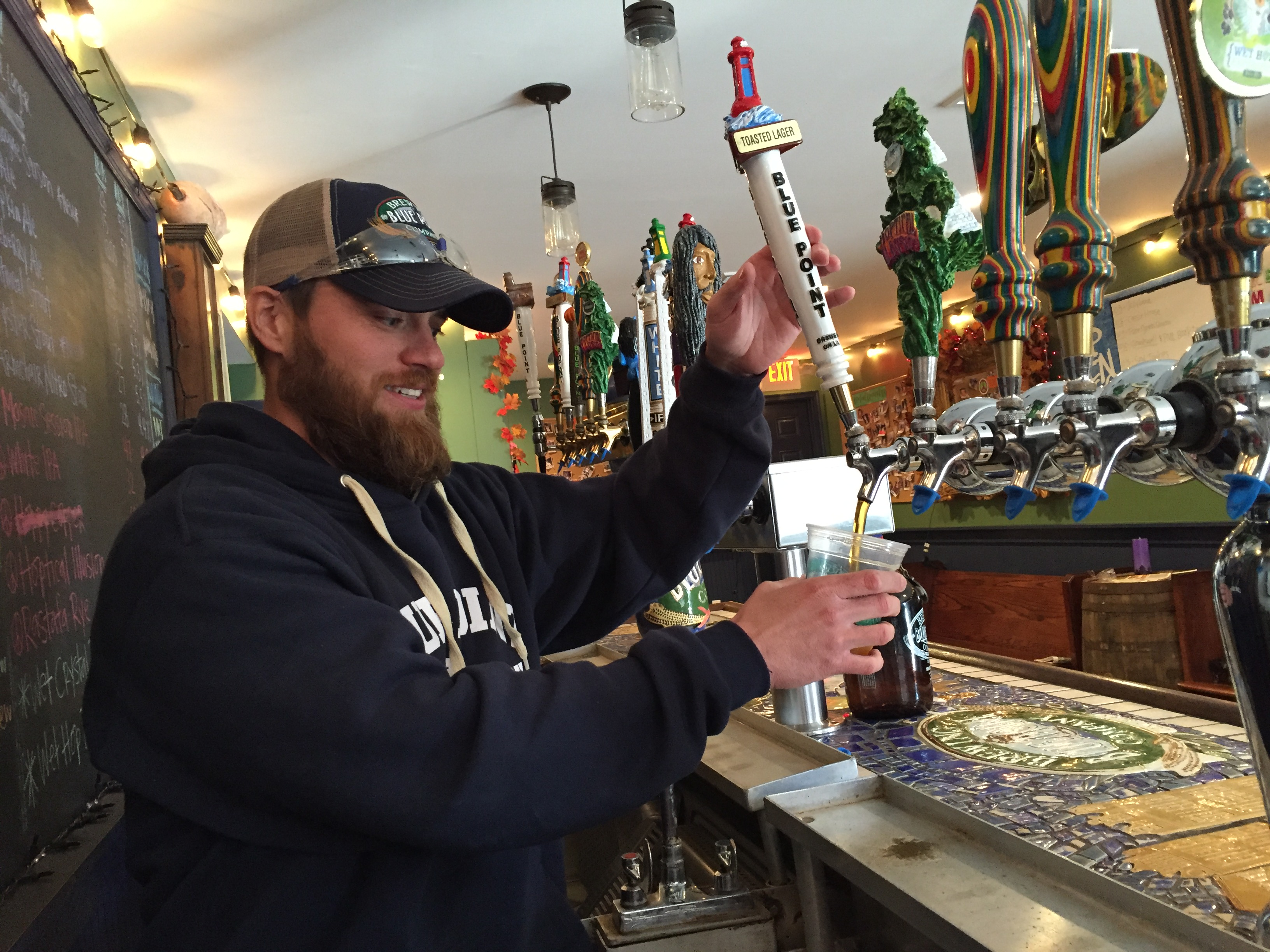 Jansen serves a beer in the tasting room at Blue Point Brewery