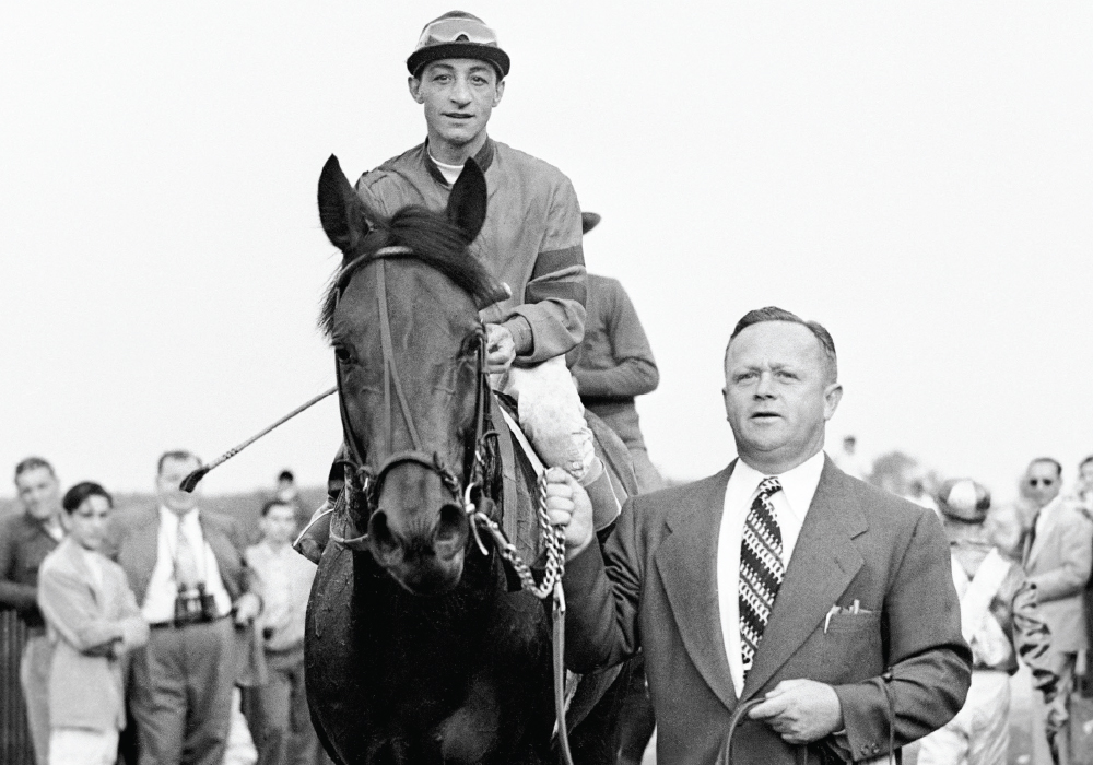 Trainer H.A. 'Jimmy' Jones leads thoroughbred Citation with jockey Edward Arcaro riding, after they won the Belmont Stakes, June 12, 1948. image: adam coglianese