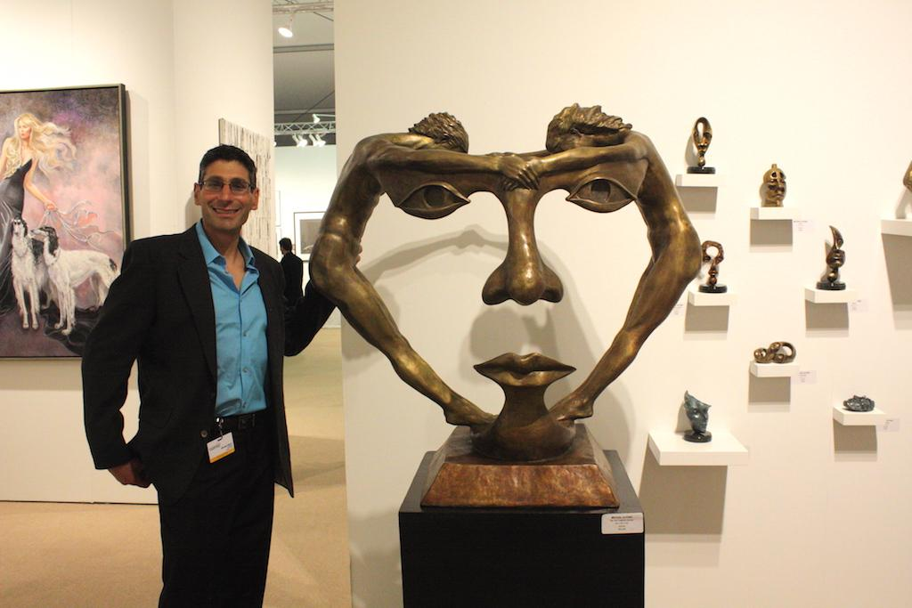 "East Meadow raised Michael Alfano pictured with his philosophical sculptures exhibited by Artblend. Alfano accredits his inspiration to the Albert Einstein quote: ""Curiosity has its own reason for existing"". His bronze sculpture ""We Two Together"" portrays a man and woman whose alignment forms a lager face within the negative space, signifying their union. image: elizabeth cantwell"