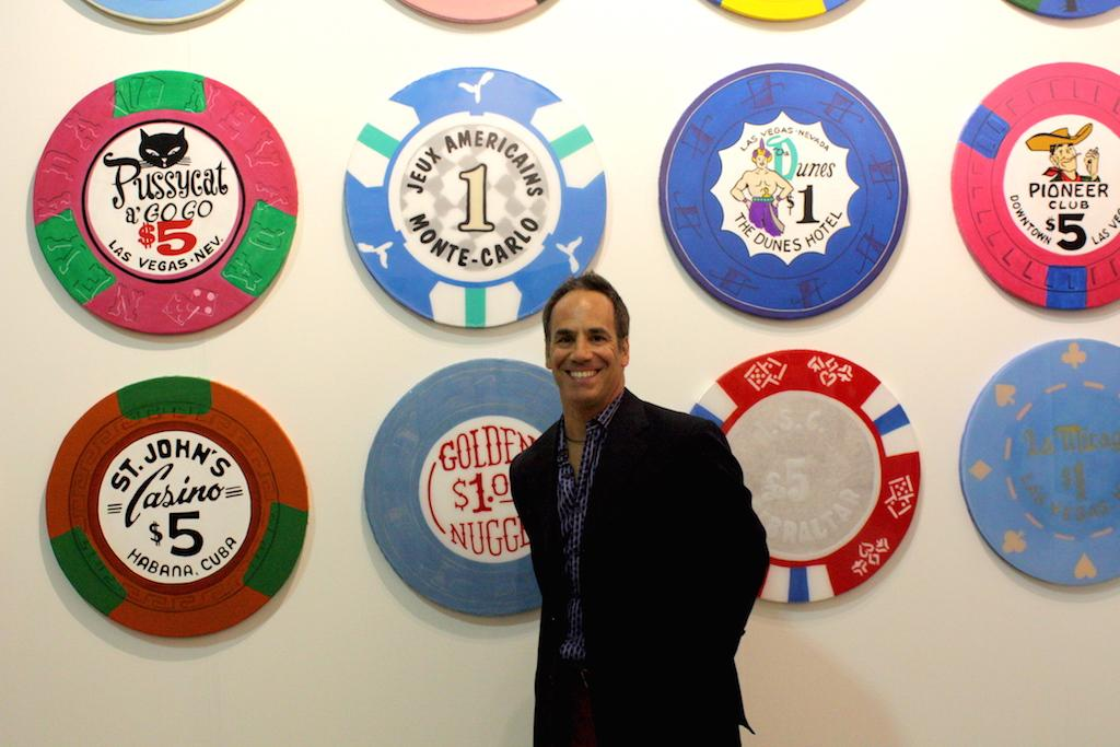 Victor Spinelli posing with his paintings of antique poker chips from Chip Series exhibited by SPiN Galleries. Each chip is created using acrylic and oil paints on wood covered by canvas. He hopes his series evokes nostalgia like his own for older casino staples. image: elizabeth cantwell
