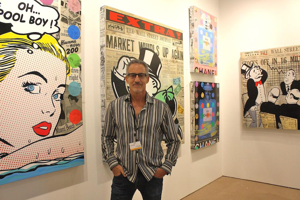 "Bruce Lowrie of Bruce Lowrie Gallery posing with works by pop iconoclast and mixed media artist Nelson De La Nuez including ""Chanel No 5"", ""High Maintenance"", ""Take the Money and Run"" and ""Wall Street Panic"". image: elizabeth cantwell"