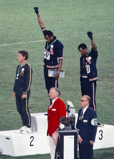The American sprinters Tommie Smith, John Carlos and Peter Norman during the award ceremony of the 200 m race at the Mexican Olympic games. During the awards ceremony, Smith and Carlos protested against racial discrimination: they went barefoot on the podium and listened to their anthem bowing their heads and raising a fist with a black glove. Mexico City, Mexico, 1968 Mexico city, Mexico, 1968