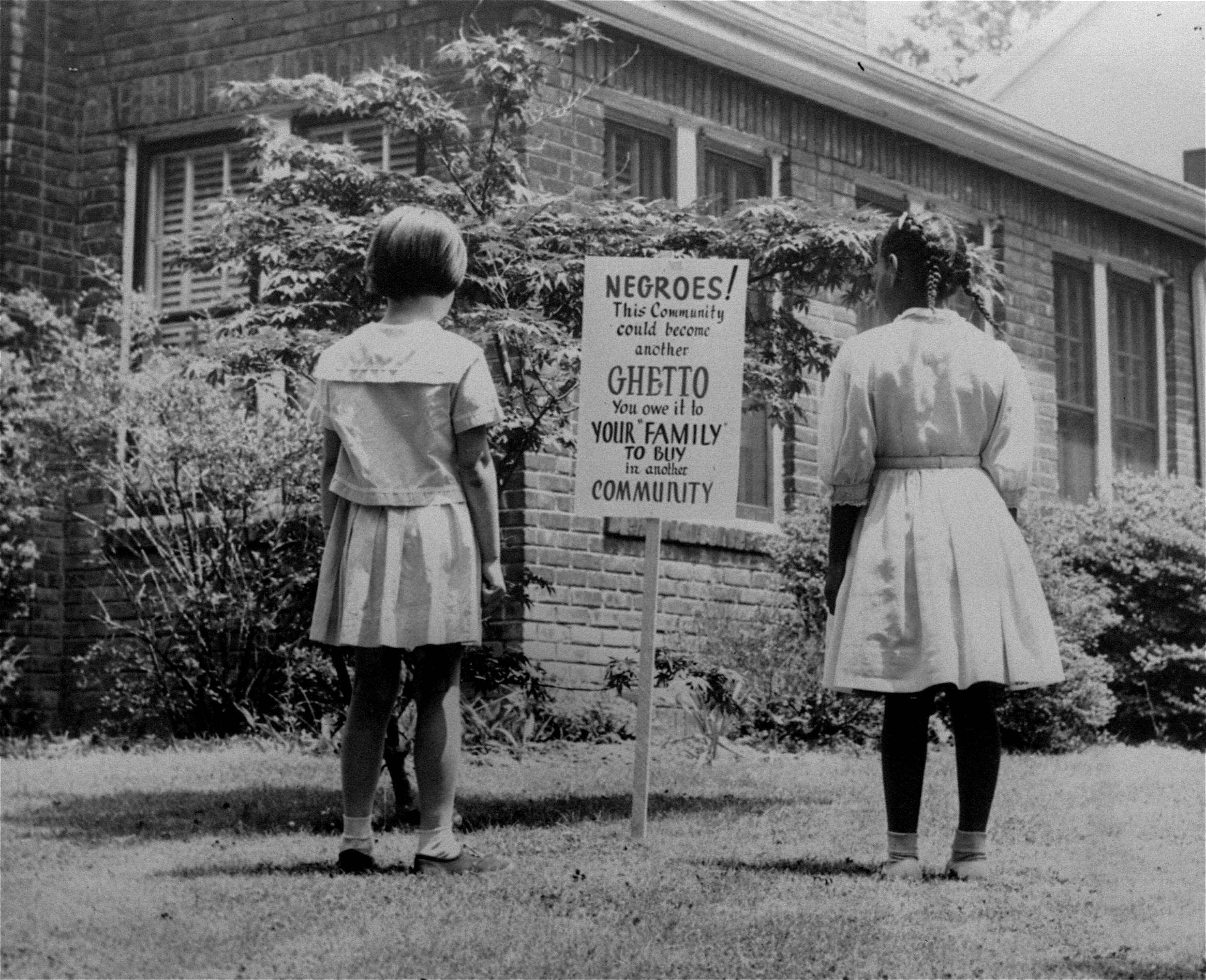 "An African American and a white girl study a sign in the integrated Long Island community of Lakeview, N.Y., April 1962. It reads ""Negroes! This community could become another ghetto. You owe it to your 'family' to buy in another community."" The sign was an attempt to keep African Americans from exceeding the number of whites who want to live in an integrated town. image: ap photograph"