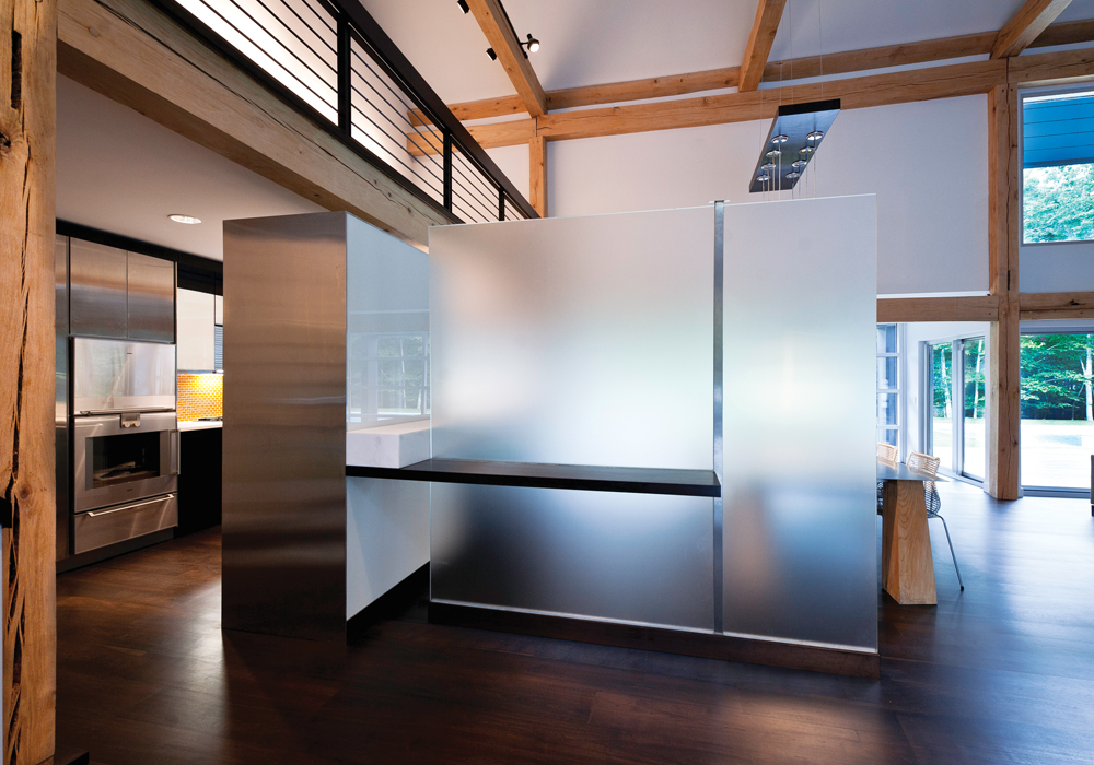 The frosted glass partition creates separation to the dining room and entryway without losing the open concept feel. The partition was designed to be wall height to match the kitchen cabinetry allowing the architectural details to be viewed throughout the entire space. image: mark stumer
