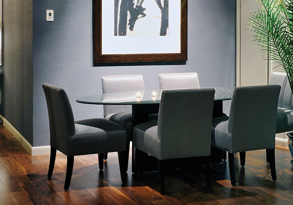 The dark navy blue accent wall helps de ne the dining room as its own space within the open floor plan.