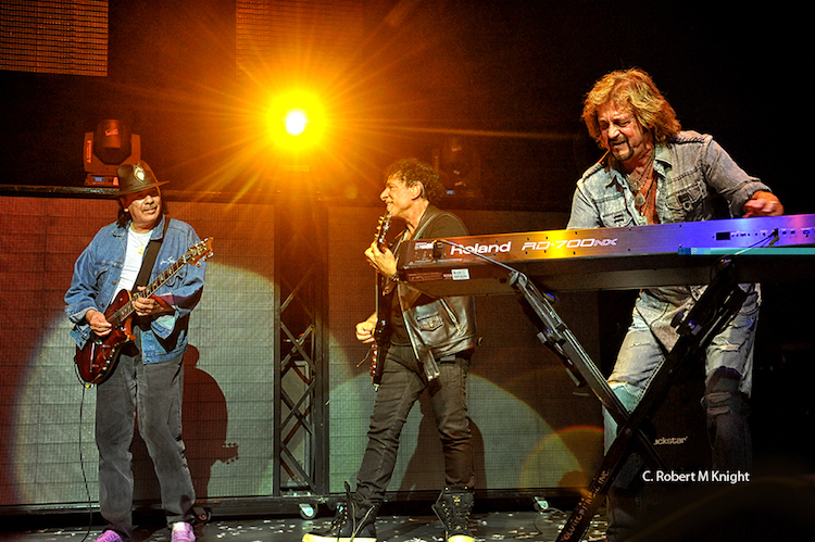 Neal Schon, Carlos Santana and Gregg Rolie on stage.