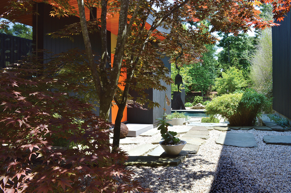 The entry courtyard is shaded by a red maple tree.
