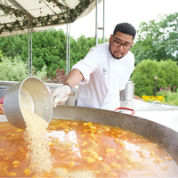 Chef Ricardo Alvarez pouring rice into Paella pan.
