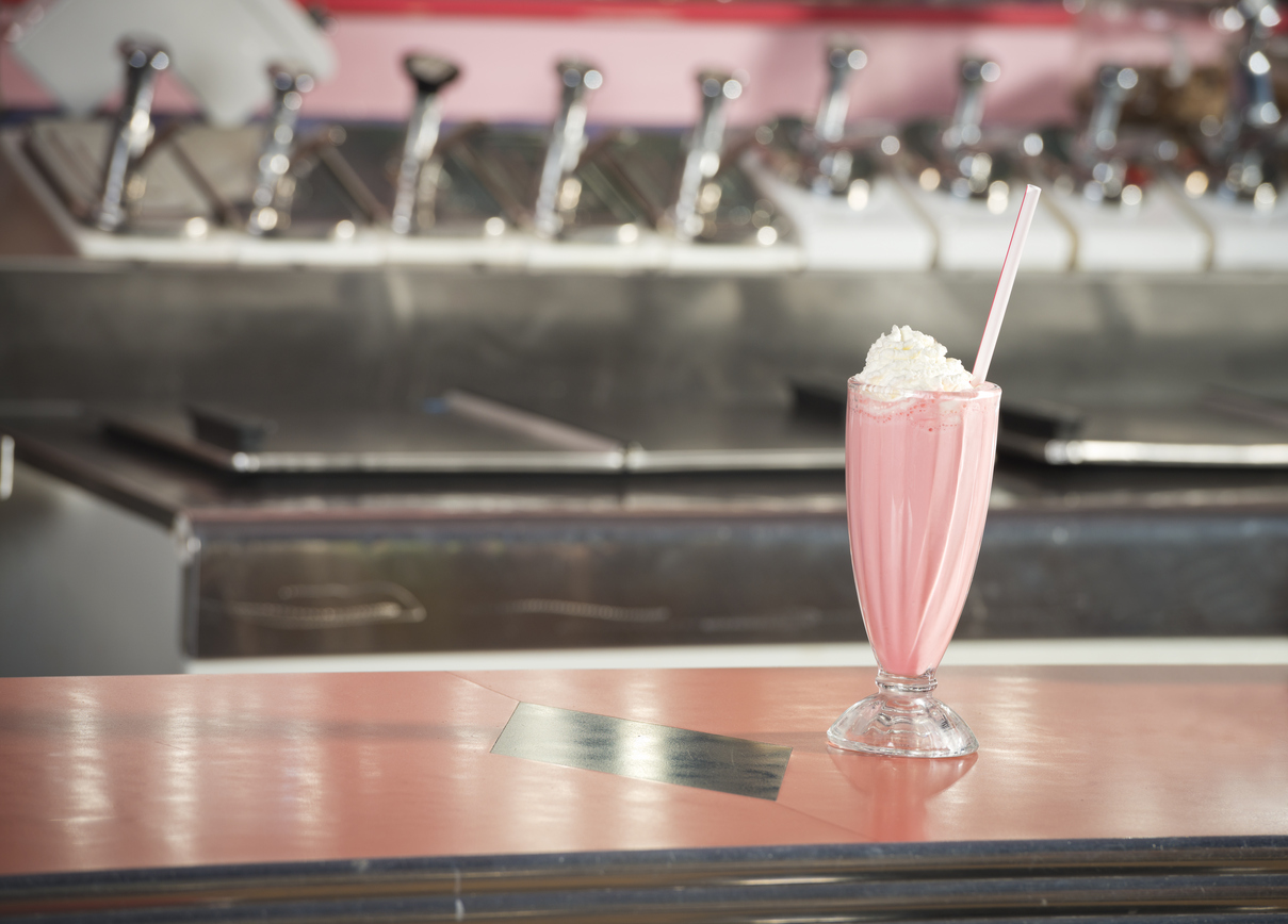 A strawberry milkshake sitting on a counter at a 1950's diner