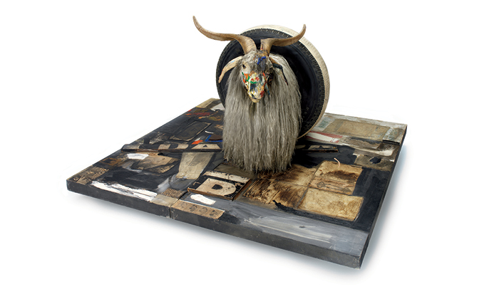 """Monogram,"" 1955–59. Oil, paper, fabric, printed reproductions, metal, wood, rubber shoe-heel and tennis ball on two conjoined canvases with oil on taxidermied Angora goat with brass plaque and rubber tire on wood platform mounted on four casters, 42 × 53 1/4 × 64 1/2 in."