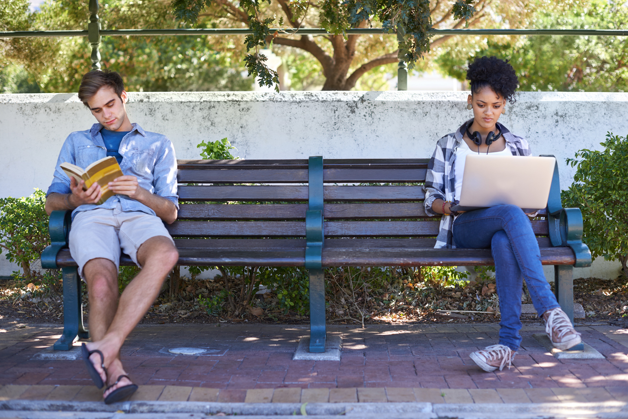 Shot of two college students studying while sitting on a bench on campus