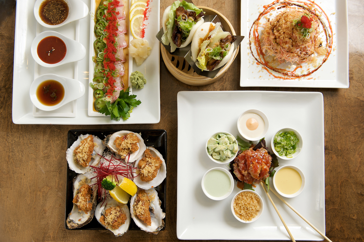 Koi Kokoro, a Japanese kitchen in Islip offers tapas-style menu items. Clockwise from top left; yellowtail jalapeno flight, Kobe pork belly bun, Miru mountain specialty roll, toro tartar and fried oysters. (Feb. 5, 2015) Credit: Doug Young