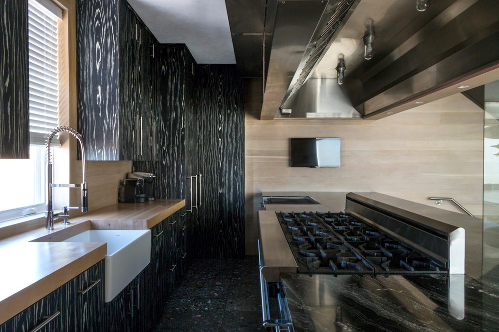 The galley-style kitchen features a large indoor grill, 10-burner stove, ovens, refrigerator drawers, warming drawers, beverage drawers and lots of workspace, all with a commercial grade exhaust hood above.